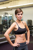 Fit brunette in black sports bra looking at camera