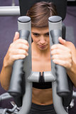 Serious brunette using weights machine for arms