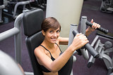 Happy brunette using weights machine for arms