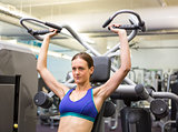 Fit focused brunette using weights machine for arms