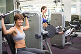 Healthy happy brunette using weights machine for arms