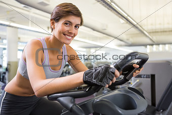 Fit smiling brunette working out on the exercise bike