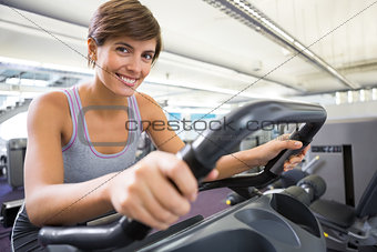 Smiling brunette working out on the cross trainer
