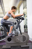 Fit brunette working out on the exercise bike