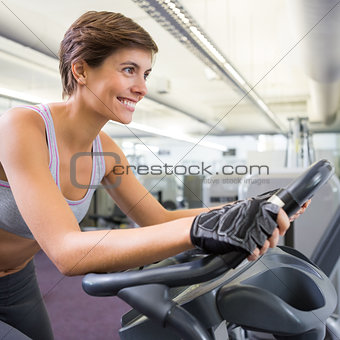 Fit smiling woman working out on the exercise bike