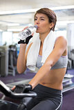 Fit woman taking a drink on the exercise bike