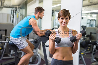 Fit brunette lifting weights smiling at camera