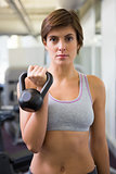 Fit brunette lifting kettlebell looking at camera