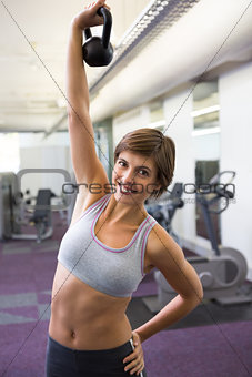 Fit brunette lifting kettlebell smiling at camera