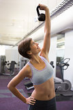 Fit brunette lifting kettlebell and smiling