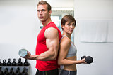Fit couple lifting dumbbells together looking at camera