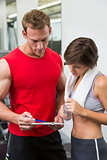 Handsome personal trainer with his client looking at clipboard