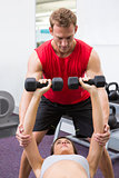 Personal trainer helping client lift dumbbells