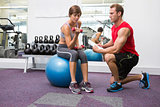 Personal trainer with client sitting on exercise ball lifting dumbbell