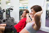 Fit couple doing sit ups on exercise ball