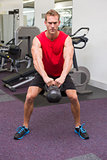 Strong man lifting heavy kettlebell