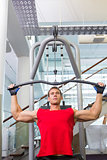 Strong man using weights machine for arms