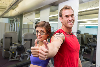 Fit attractive couple smiling at camera showing thumbs up
