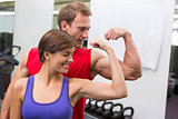 Fit attractive couple flexing their biceps
