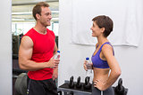 Fit attractive couple chatting holding water bottles