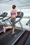 Fit brunette running on the treadmill
