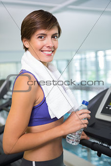 Fit brunette smiling at camera on the treadmill