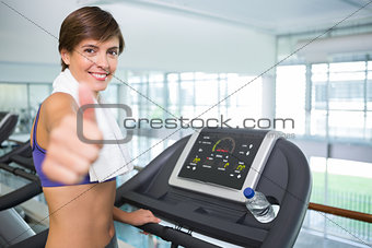Fit brunette smiling at camera on the treadmill showing thumbs up