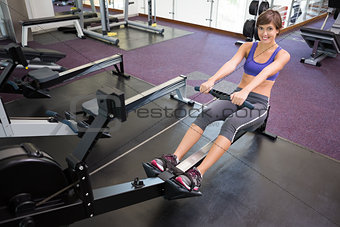 Fit smiling brunette working out on rowing machine