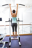 Fit brunette hanging from bars