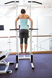 Fit brunette supporting her weight on bars
