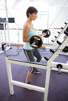 Fit brunette holding heavy barbell