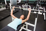 Fit brunette lifting heavy barbell lying on bench