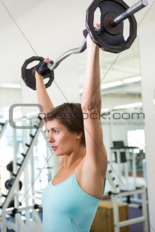 Fit brunette lifting heavy barbell over head