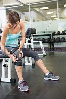 Fit brunette sitting on bench holding injured knee