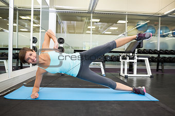 Fit smiling brunette doing pilates on exercise mat