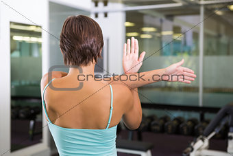 Fit brunette stretching her arms
