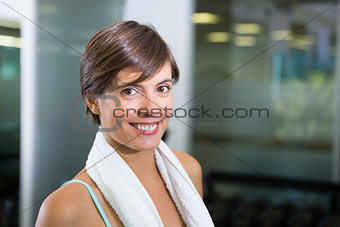Fit brunette smiling at camera with towel around shoulders