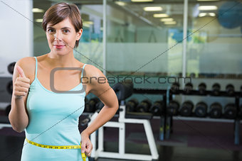 Fit brunette smiling at camera with measuring tape around waist