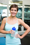 Fit brunette smiling at camera holding water bottle