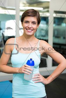 Fit brunette smiling at camera holding water bottle