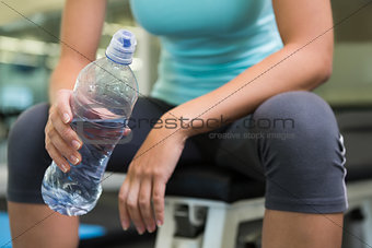 Fit woman sitting on bench holding water bottle