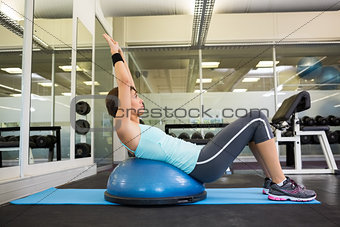 Fit brunette using bosu ball to work out