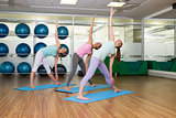 Yoga class in extended traingle position in fitness studio