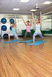 Yoga class in warrior pose in fitness studio