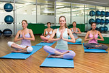 Smiling yoga class in lotus pose in fitness studio