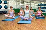 Smiling yoga class in lotus pose in fitness studio