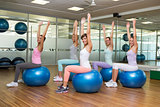 Fitness class sitting on exercise balls in studio