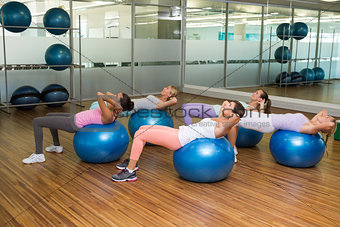 Fitness class doing sit ups on exercise balls in studio
