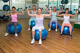 Fitness class holding dumbbells on exercise balls in studio