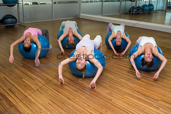 Fitness class stretching on exercise balls in studio